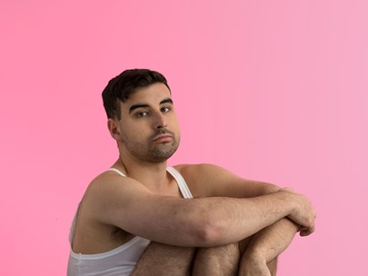 A young man wearing white underwear, sitting on a high stool, in front of a pink background.