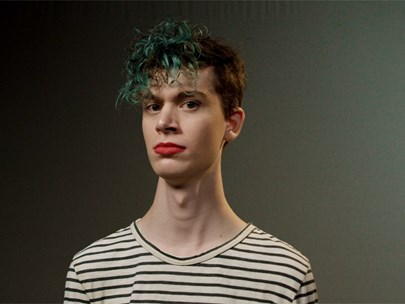 Young person staring at the camera, wearing red lipstick and with their hair dyed green.