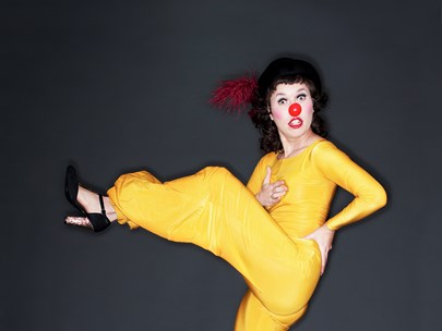 Woman in yellow pantsuit and high heels, one leg kicked high, with clown's red nose