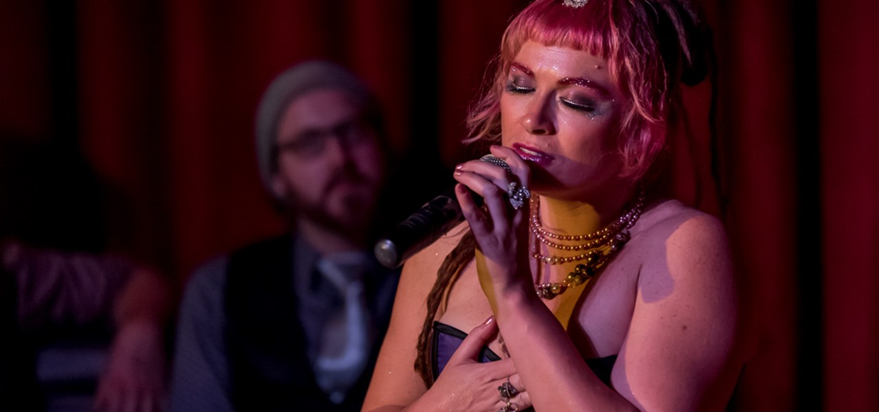 Woman singing in a soulful way, eyes closed. A bearded man is behind her, a little out of focus