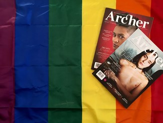 Two copies of Archer Magazine are displayed on a fabric rainbow flag.