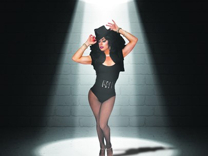 A drag queen in a black leotard standing in front of a brick wall under a down light.