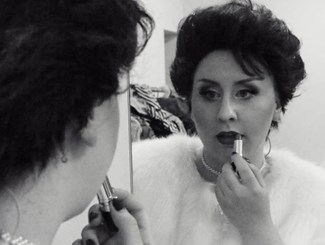 A black and white image of a woman wearing a white fur coat applying lipstick in a mirror
