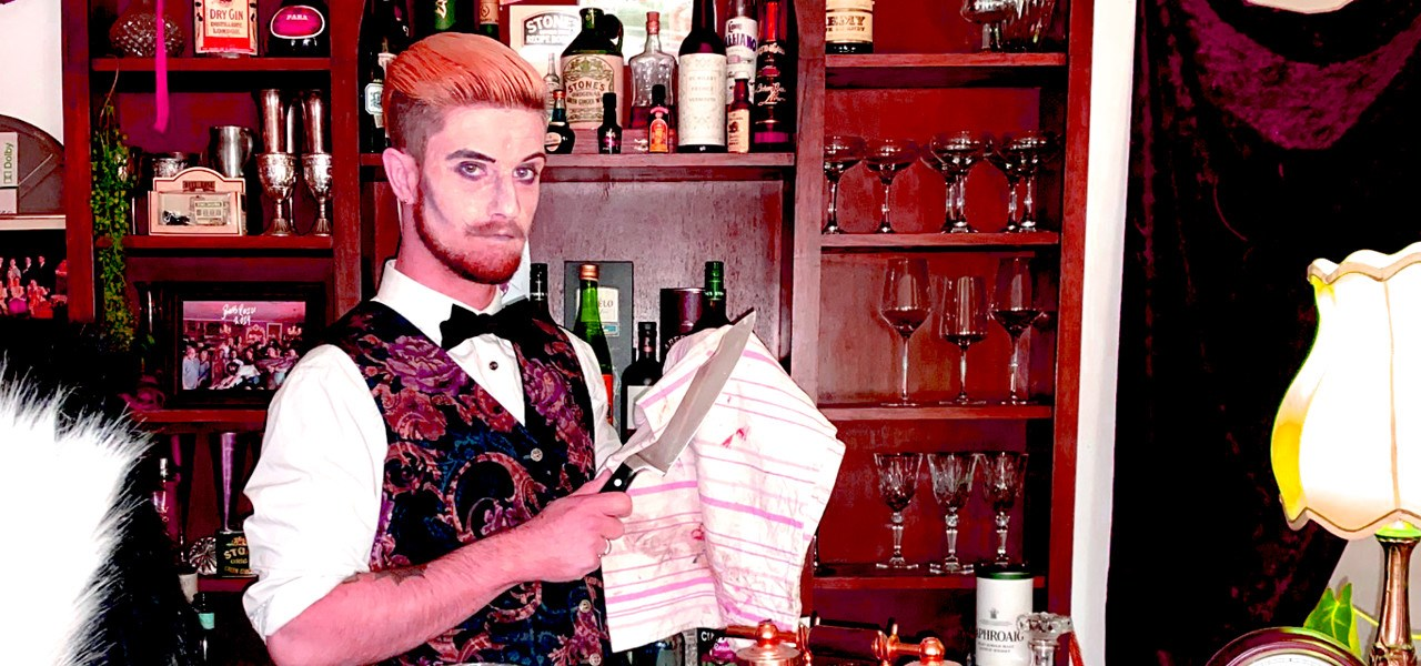 A barman stands in front of a bar, dressed in a bowtie and vest with a slicked back hair and a beard, he's polishing a blood stained knife