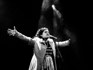 A black and white image of young person of colour speaking into a microphone with their hands out in an expressive way