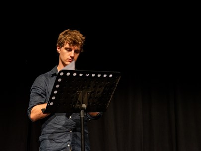 A Young Man at a Music Stand Reading a Script